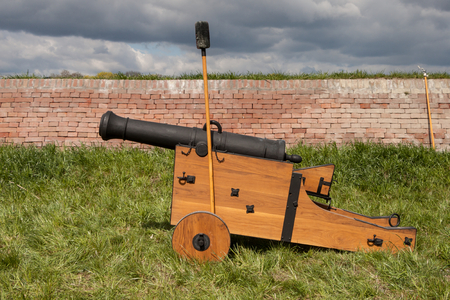 cannon gun: View of an old cannon that is built on the grass in front of a brick wall. The gun is propped up on a swab barrel