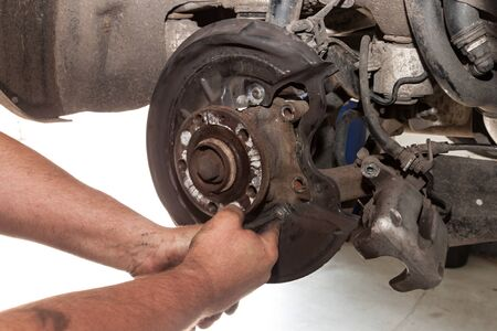 repaired: Hands mechanics repaired the brakes on a passenger car Stock Photo