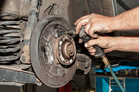 frenos: Manos mecánicos reparan los frenos en un coche de pasajeros