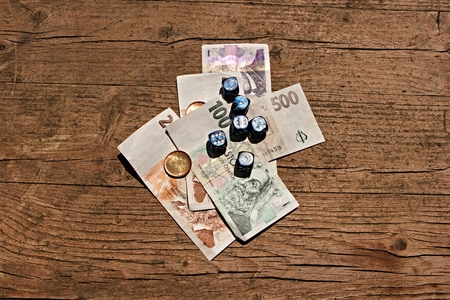 indecision: Wooden table on which are placed the dice on a few paper bills