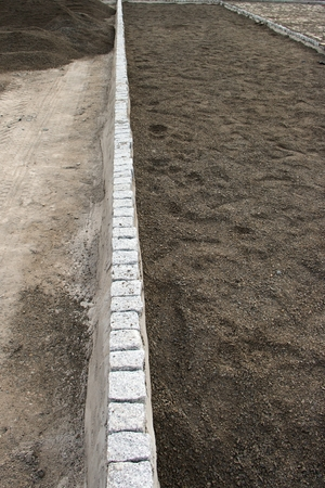 unfinished: Unfinished base pavement bordered by square blocks in concrete