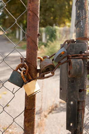 rusty chain: Several locked padlocks associated with a rusty chain, closed steel door frame