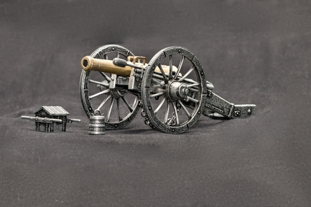 wheel barrel: Old metal replica guns and accessories on a dark background