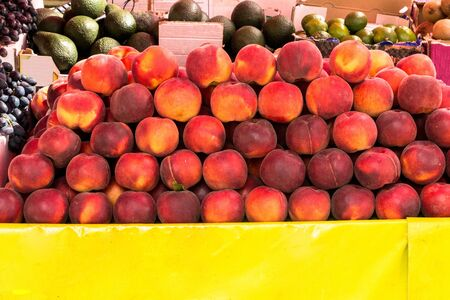 On a table with a yellow tablecloth is a balanced pile of juicy, ripe peaches 写真素材