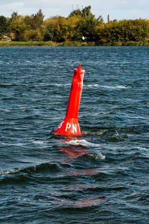 A warning red buoy swaying in the waves near the shore