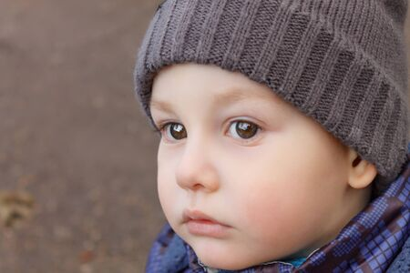 Thoughtful child looking to the left. Face close-up. Young boy outdoors wearing a cap.