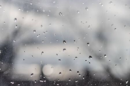 Raindrops on glass, wet city window, rain in the city outside the window Imagens
