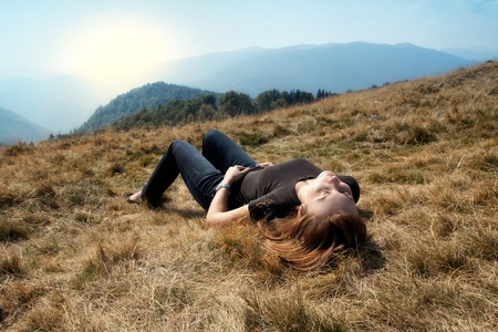 Mountain woman laying in the grass.
