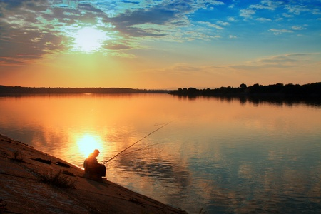 Fishing at sunset, serene scene.