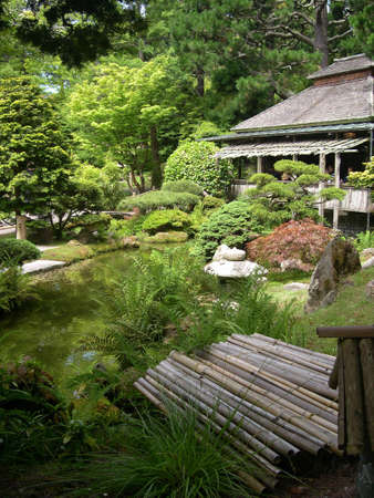 Sunny day in a beautiful Japanese garden with tea house overlooking a pond.           Stock Photo - 1200822