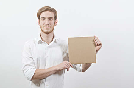 young adult man: Young Adult Man in White Shirt Holding a Cardboard Inscription