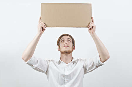 young adult man: Young Adult Man in White Shirt Holding a Big Cardboard Inscription Above His Head, Looking Up at It Stock Photo