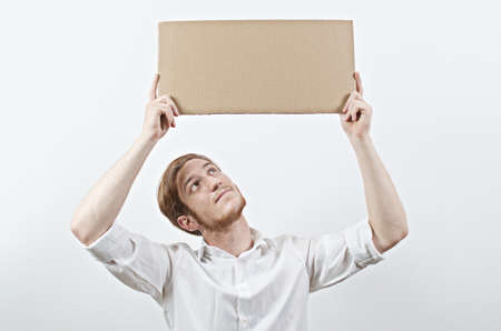 young adult man: Young Adult Man in White Shirt Holding a Big Cardboard Inscription Above His Bent Head, Looking Up at It Stock Photo