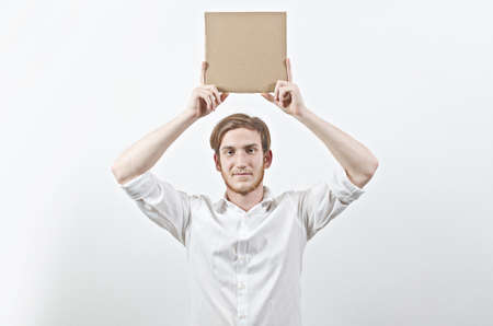 young adult man: Young Adult Man in White Shirt Holding a Big Cardboard Inscription Above His Head
