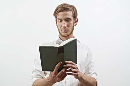 diligente: De pie Hombre adulto joven en camisa blanca sostiene un libro en sus manos, Lectura