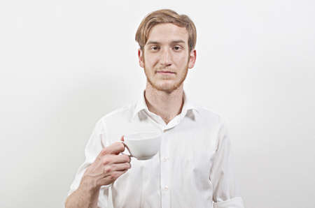 young adult man: Young Adult Man in a White Shirt Holding a Cup of Coffee in His Hand Stock Photo