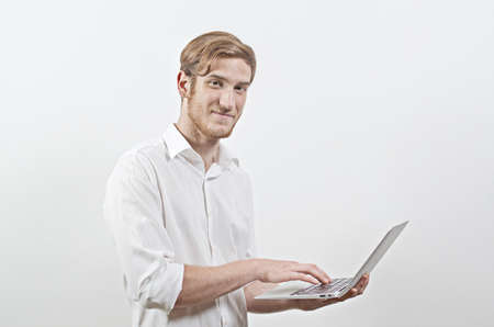 young adult man: Standing Young Adult Man in a White Shirt, Holding a Laptop Stock Photo