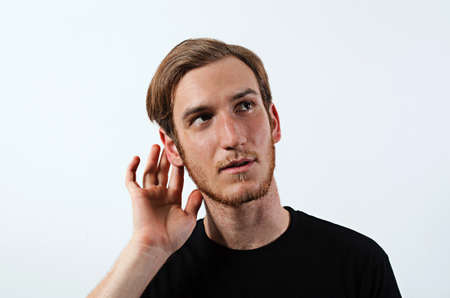 paying attention: A Young Adult Male Wearing Dark T-Shirt with His Hand Near His Ear, Gestures Can Not Hear or Talk Louder Stock Photo