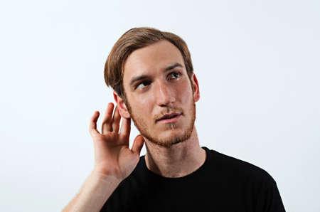 poner atencion: Un joven macho adulto llevando la camiseta oscura con su mano cerca de su oído, gestos no pueden oír o hablar más alto