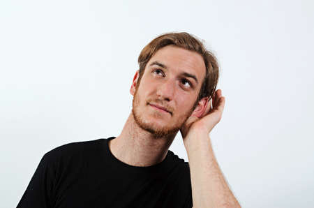 talk to the hand: A Young Adult Male Wearing Dark T-Shirt with His Hand Near His Ear, Gestures Can Not Hear or Talk Louder Stock Photo