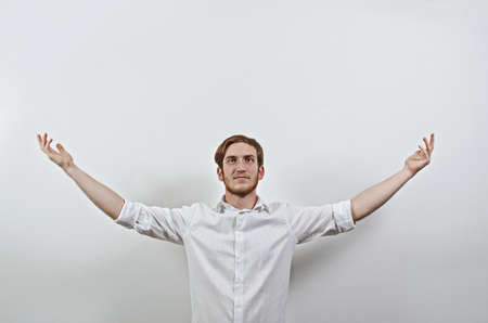 Young Adult Male in White Shirt Gesturing Arms Wide Open