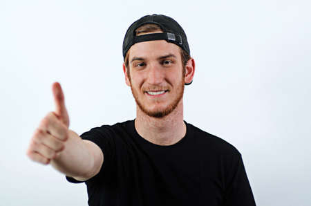Smiling Young Adult Male in Dark T-Shirt and Baseball Hat Worn Backwards Shows His Thumbs Up