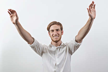 enrolled: Smiling Joyful, Very Happy Young Man in White Shirt, Arms Raised Stock Photo