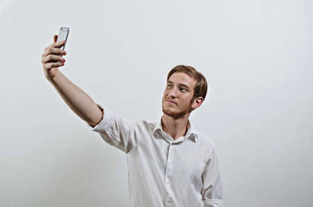 young adult man: Young Adult Man in White Shirt Takes a Selfie with His Phone