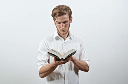 Standing Young Adult Man in White Shirt Holds a Book in His Hands, Reading