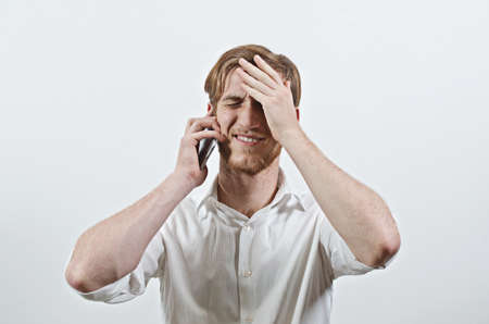 Young Adult Man in White Shirt Listening to His Phone, Holding His Head in Hand, Receiving Bad News Stock Photo