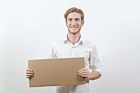 young adult man: Young Adult Man in White Shirt Holding a Big Cardboard Inscription