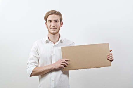 Young Adult Man in White Shirt Holding a Big Cardboard Inscription