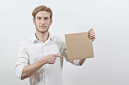 young adult man: Young Adult Man in White Shirt Holding a Cardboard Inscription And Pointing at It