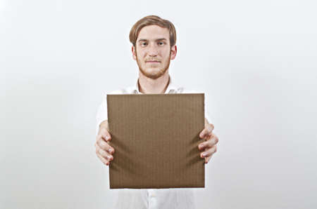 young adult man: Young Adult Man in White Shirt Holding a Square Shaped Cardboard Inscription in Front of His Body