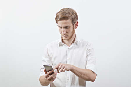 young adult man: Young Adult Man in White Shirt Using His Smart Phone