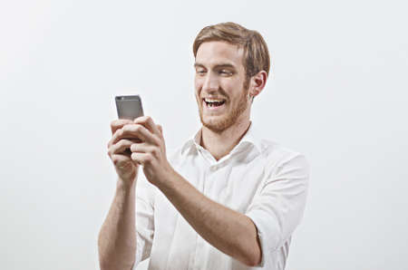 young adult man: Very Happy Smiling Young Adult Man in White Shirt Looking at His Mobile Phone