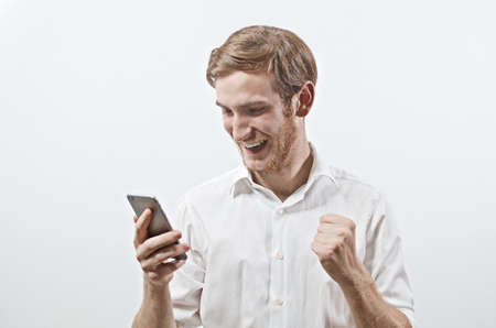 Very Happy Smiling Young Adult Man in White Shirt Looking at His Mobile Phone
