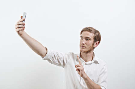 young adult man: Young Adult Man in White Shirt Takes a Selfie with His Smart Phone