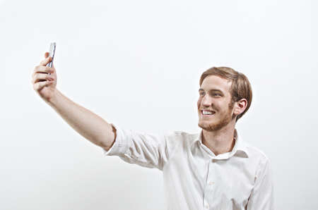 young adult man: Young Smiling Adult Man in White Shirt Takes a Selfie with His Smart Phone Stock Photo
