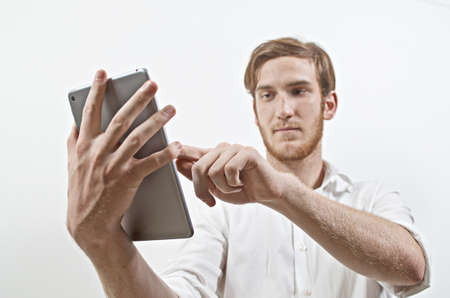 pointing device: Young Adult Male in White Shirt Using Digital Tablet Stock Photo