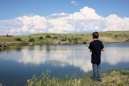 Young boy fishing at the edge of a pond with beautiful sky reflection in the water. photo
