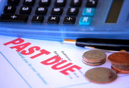 schuld: Vervallen bericht met rekenmachine en slechts een kleine hoeveelheid kleingeld beschikbaar. Stockfoto