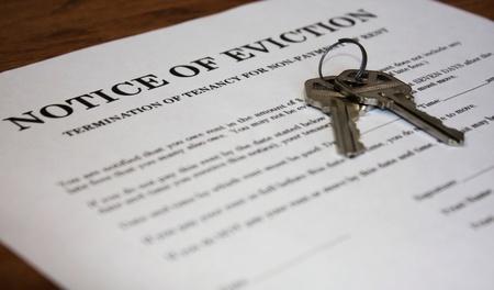 Carta indicando el aviso de desalojo con llaves de casa Foto de archivo