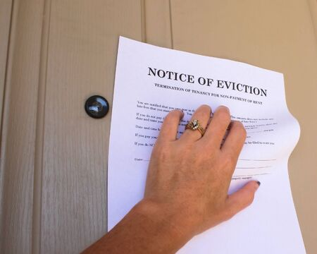 eviction: Womans hand grabbing a letter stating Eviction Notice off a house door.