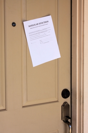 stating: Letter stating Notice of Eviction hanging on front door of house. Stock Photo