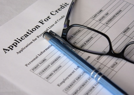 Credit application form with blue pen and glasses on a white background. photo