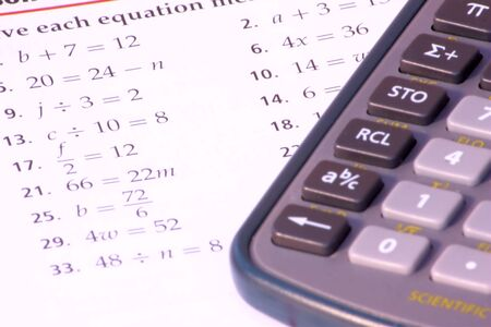 test paper: Close up shot of math homework with calculator near by. Stock Photo