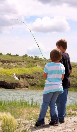 shore line: Young children fishing at the edge of a river with a small fish on the line. Stock Photo