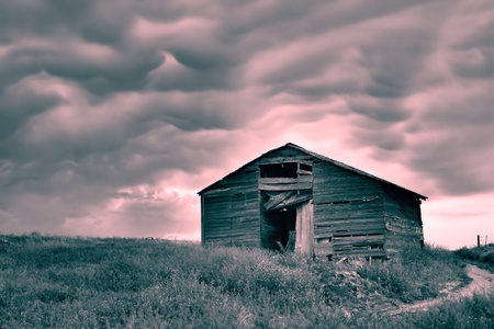 run down: Old run down barn sitting on a prairie with pink storm clouds. Stock Photo