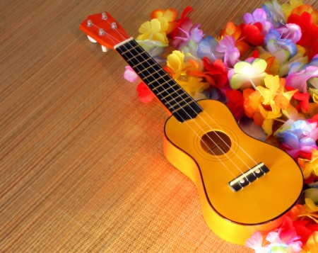 lei: Ukelele surrounded by Hawaiian style leis cast in golden sunlight. Stock Photo